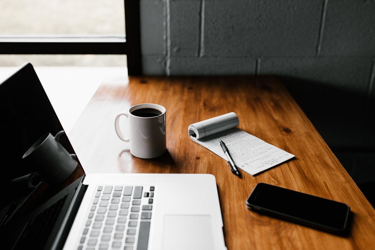 MacBook Pro, white ceramic mug, and black smartphone on table - Credit to @andrewtneel, image supplied via Unsplash