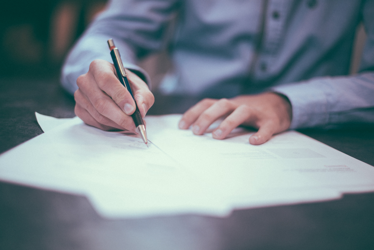Person signing document - Credit to @homajob, image supplied via Unsplash
