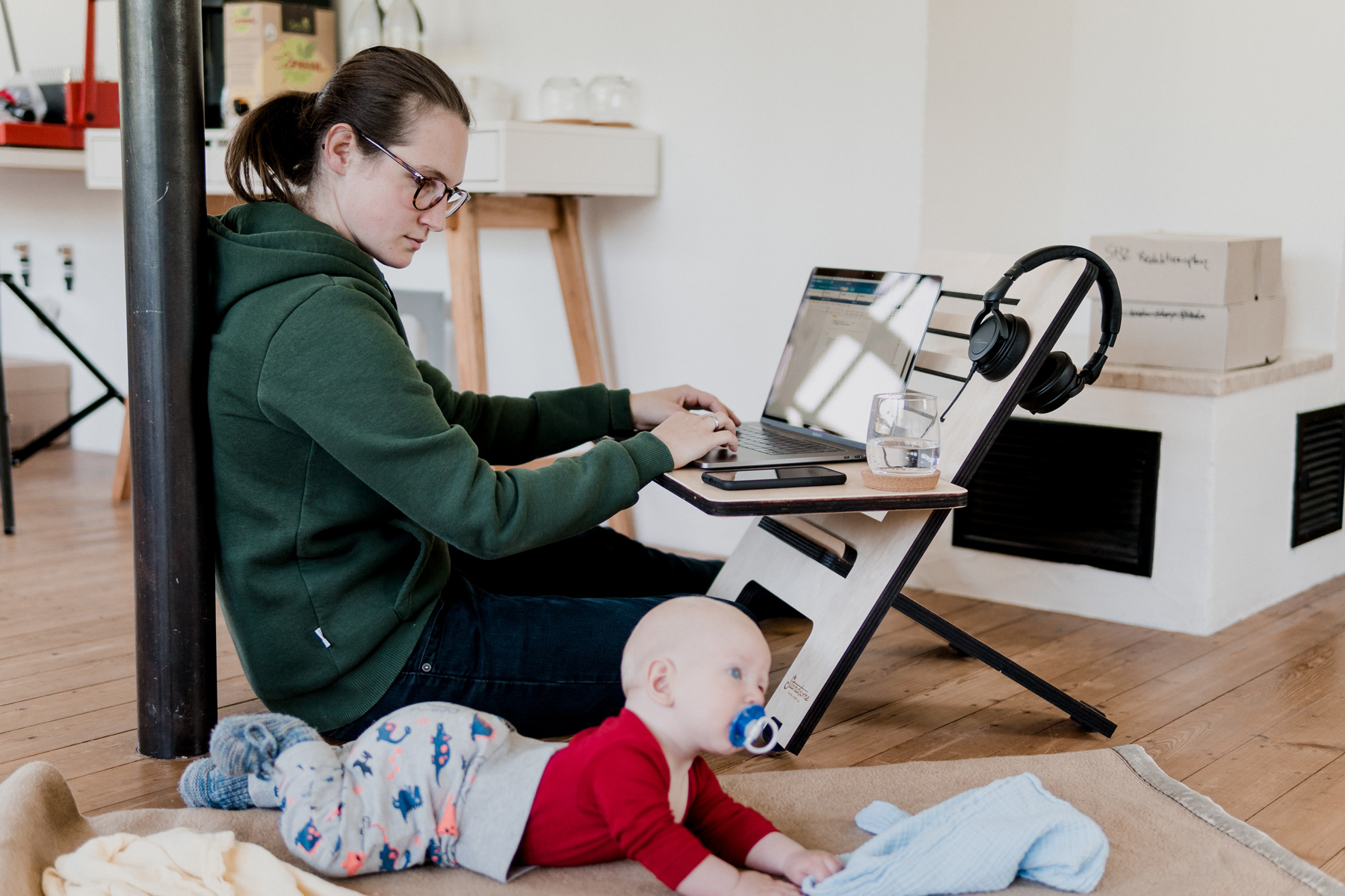 Woman working from home with baby by her side - Credit to @standsome, image supplied via Unsplash