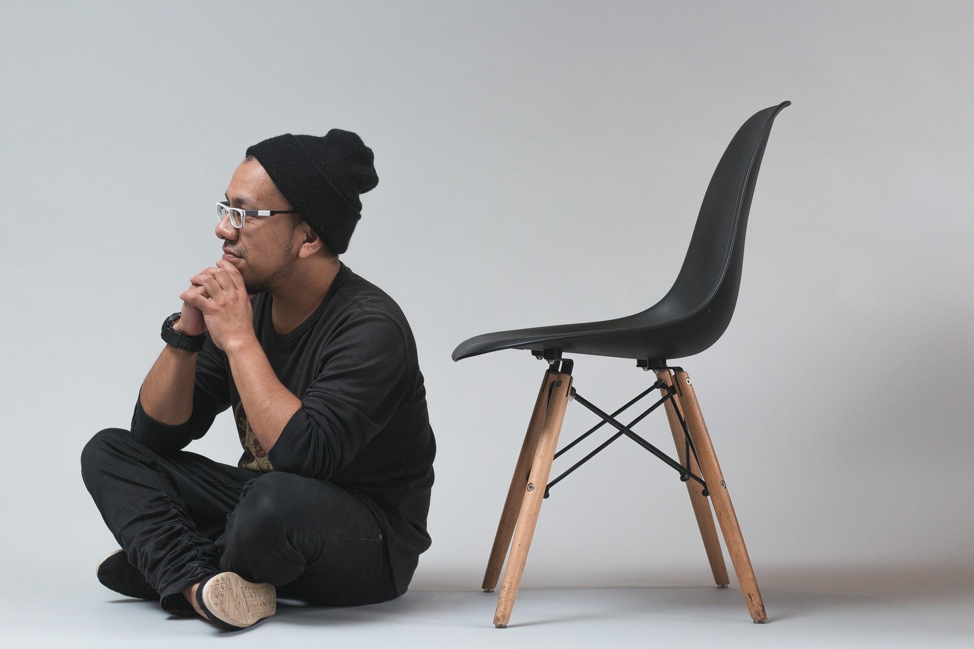 Man sitting next to chair. Photo by @josealjovin via Unsplash