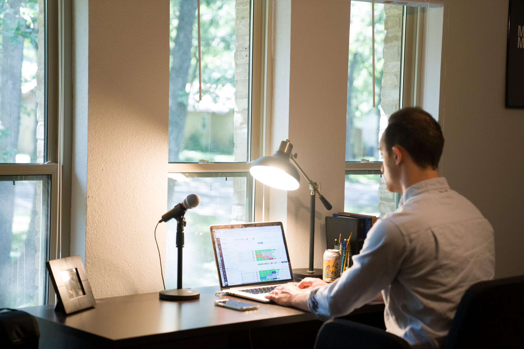 man sitting at desk working using laptop in home office - Credit to @ianharber, image supplied via Unsplash