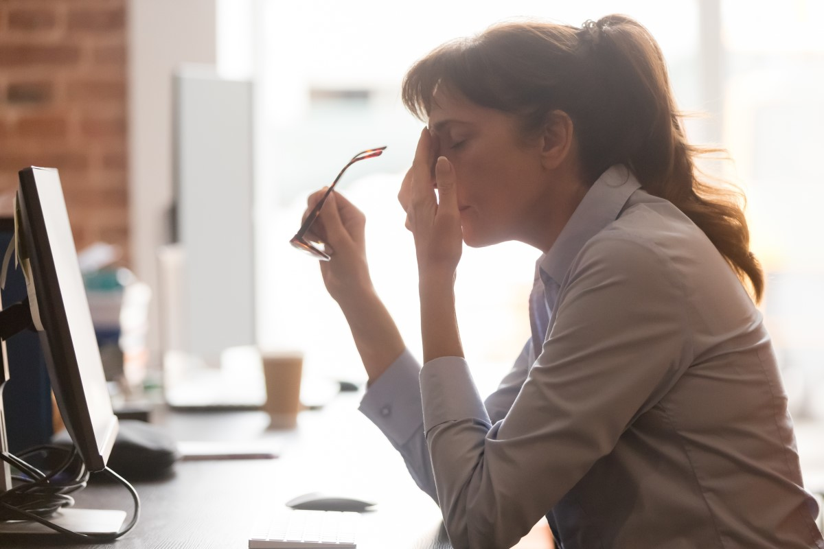 Tired female coworker sitting at desk. Photo by Fizkes via Shutterstock