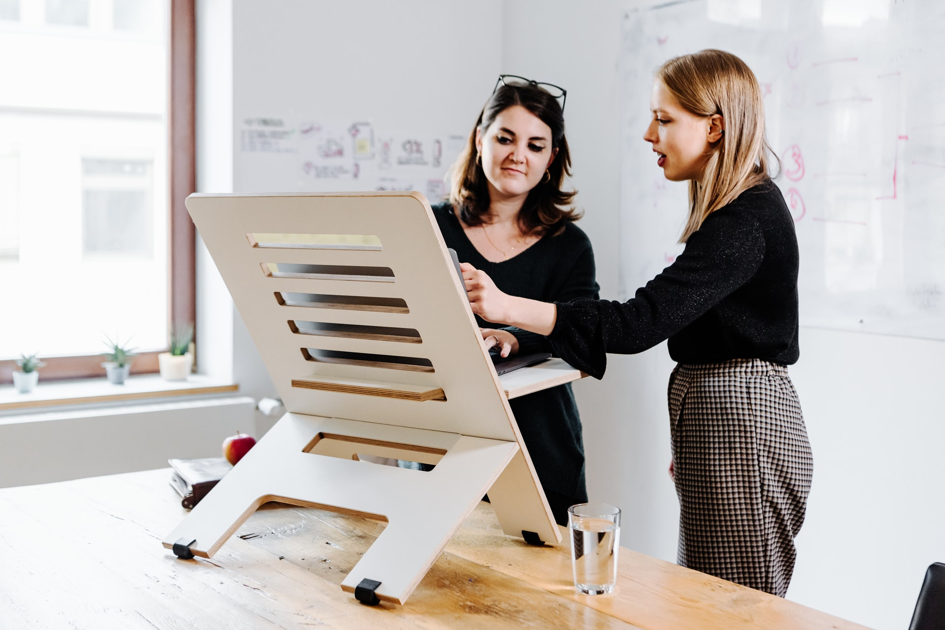 Two colleagues working at a standing desk. Photo by @standsome via Unsplash.